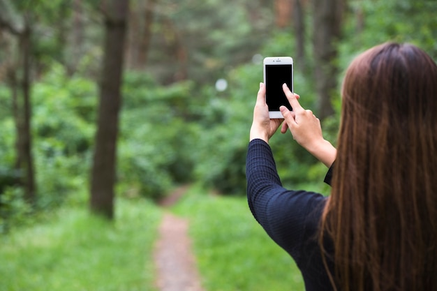 Rear view of a woman standing in the forest touching the cellphone screen