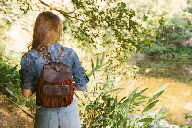 Rear view of a woman standing in forest