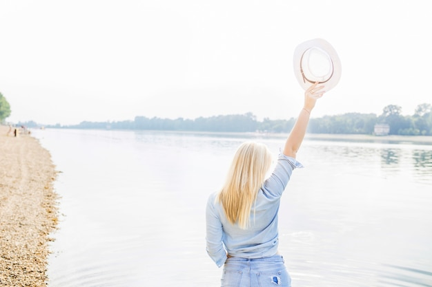 Rear view of woman standing near the lake raising hand holding hat