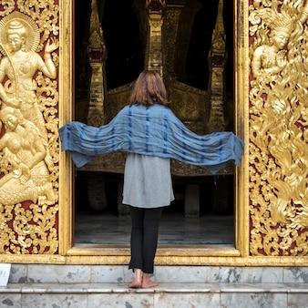 Rear view of woman standing at temple, wat xieng thong, luang prabang, laos