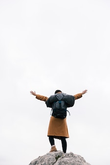 Rear view of a woman standing on the top of mountain raising her arms against sky