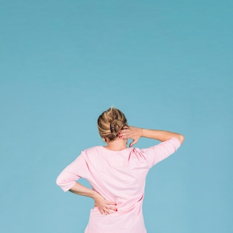 Rear view of woman suffering from backache and shoulder ache against blue wallpaper