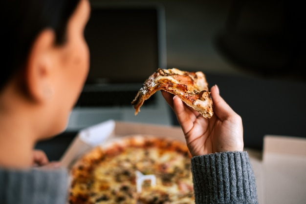 Rear view of woman taking a slice of pizza.