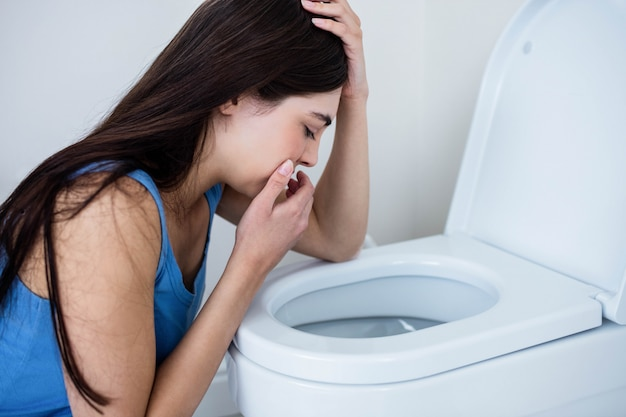 Rear view of woman throwing up in toilet