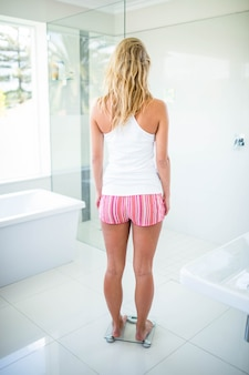Rear view of woman on weighting scale in bathroom