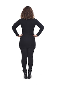 Rear view of a woman on white hands on hips