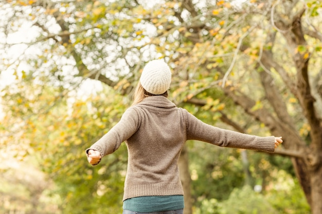 Rear view of a woman with arms outstretched on an autumns day