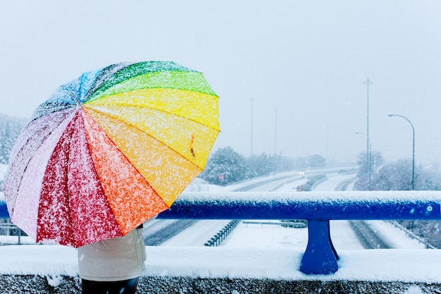 Rear view of a woman with colorful umbrella facing a snowy highway