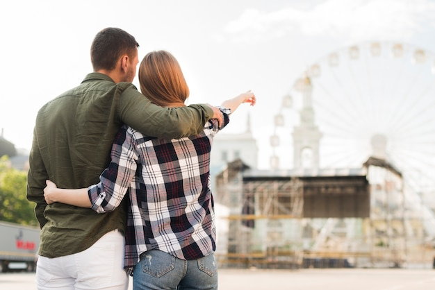 Rear view of woman with her boyfriend pointing at ferris wheel while