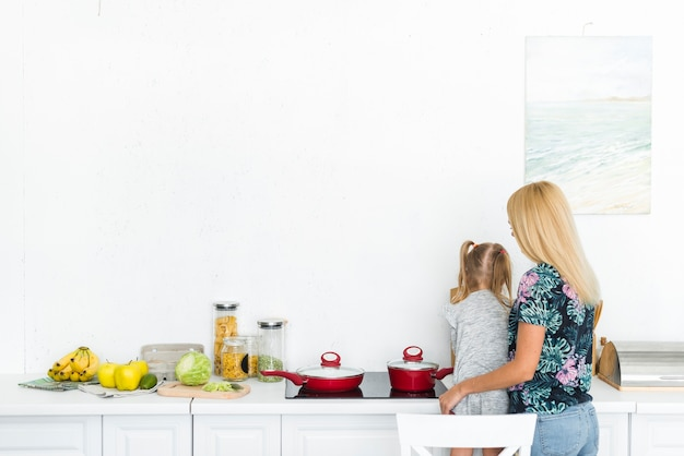 Rear view of a woman with her daughter in kitchen