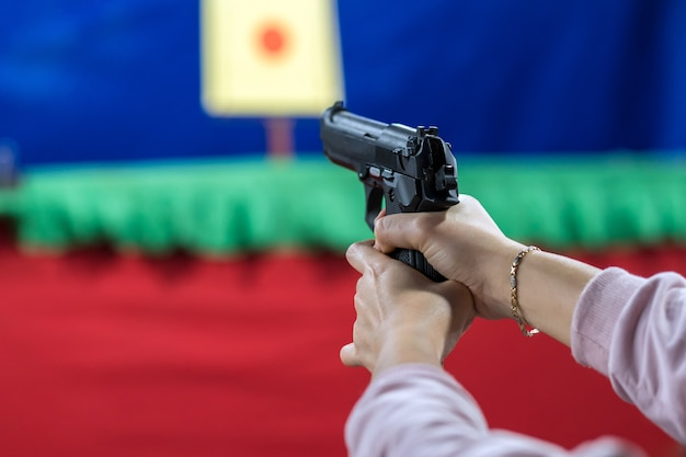 Rear view of woman with her gun on shooting at the target