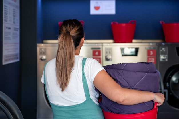 Rear view of a woman with a laundry basket in a laundromat.
