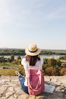 Rear view of a woman with rucksack looking at view