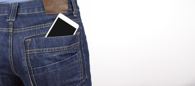Rear view of woman with smartphone in a pocket of jeans.