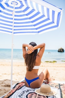 Rear view of woman with tanned skin posing at beach in sunny day. portrait from back of stylish girl in blue bikini sitting under umbrellas on sea background.
