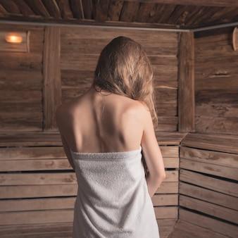 Retrovisione della donna avvolta in asciugamano bianco che sta alla sauna calda