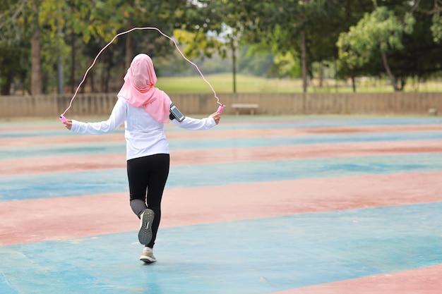 緑の木の背景で運動のために屋外でロープを立ってスキップするスポーツウェアの若いアジアのイスラム教徒の女性の背面図。