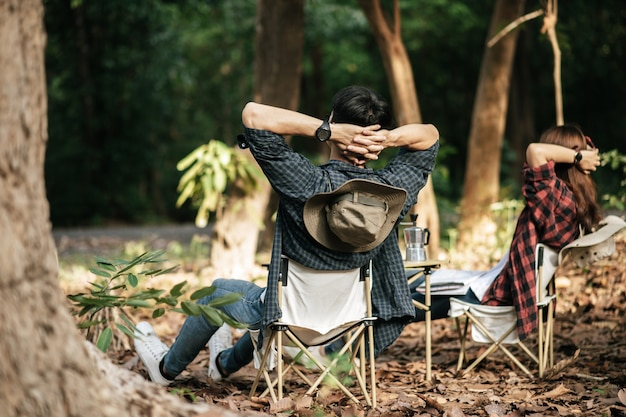 Rear view, young asian teenager couple have relax time with camping trip, they are sitting and hands on back of neck on chair in front of backpack camping tent in forest