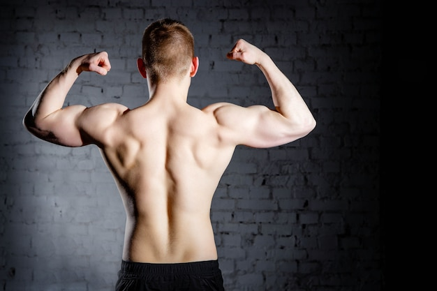 Rear view of young attractive caucasian muscular bodybuilder man