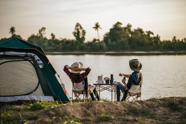 Rear view of young backpacker couple sitting to relax at front of the tent near the lake with coffee set and making fresh coffee grinder while camping trip on summer vacation