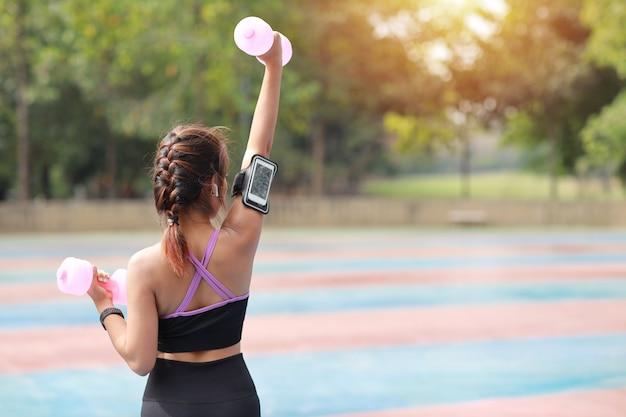Женщина молодой красоты вид сзади азиатская в спортивной одежде стоя и поднимая гантели внешние для утренней тренировки.