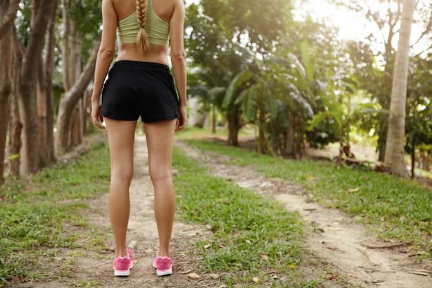 Vista posteriore del giovane atleta donna bionda in scarpe da corsa rosa in piedi nel parco o foresta sul percorso con alberi verdi intorno.