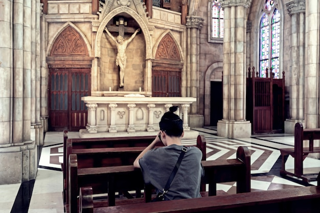 Rear view of young casual man praying in a church.