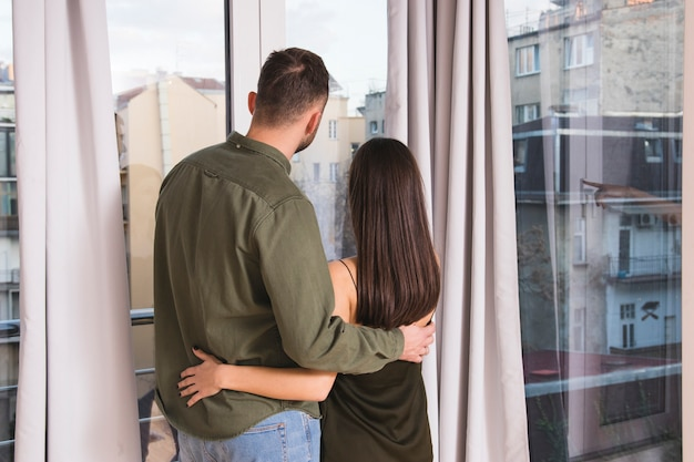 Rear view of young couple embracing looking out of window