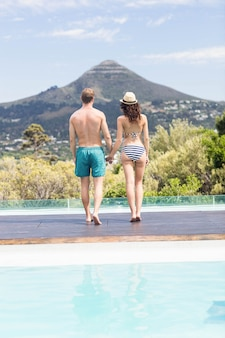 Rear view of young couple holding hands and walking together near pool on a sunny day
