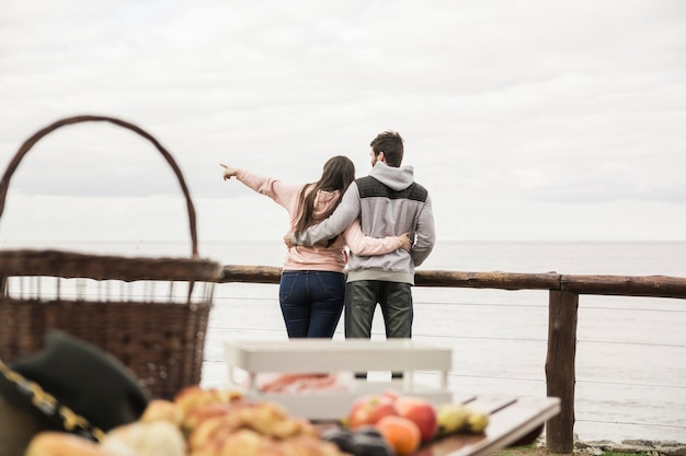 Rear view of young couple overlooking the sea