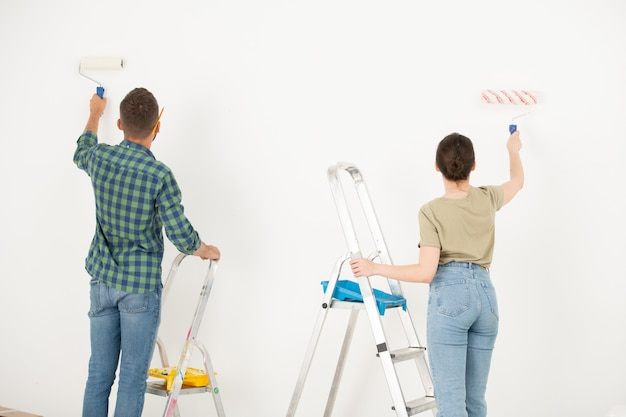 Rear view of young couple painting wall white using paint roller while remodeling their old room