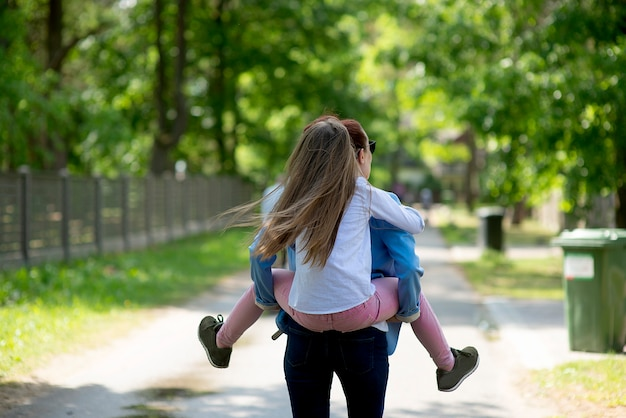 Rear view on young daughter on a piggy back ride with her mother