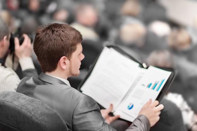 背面図。若い起業家はビジネス会議でスピーカーに耳を傾けます