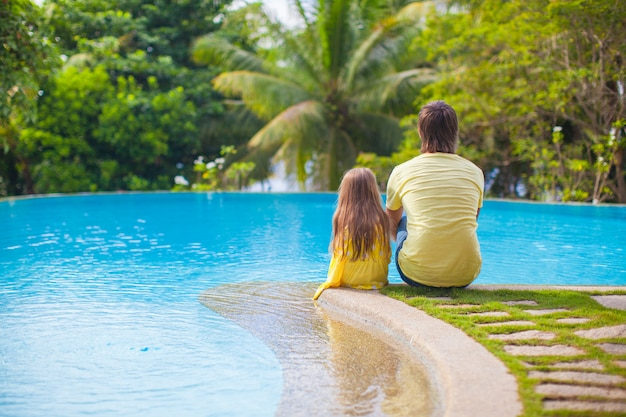 Rear view of a young father and his cute daughter sitting by the  swimming pool