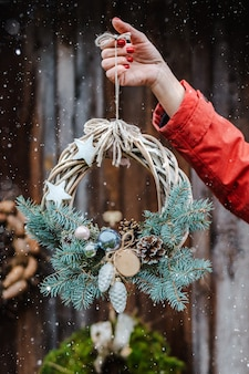 Rear view of young female hipsters decorate home for christmas at the door outside. beautiful christmas tree wreath on old wooden rustic background.