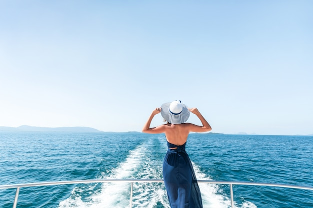 Rear view: a young girl in a blue dress is standing, raising her hands on the edge of a yacht and admiring the scenery of the azure sea. travel and vacation. copy space