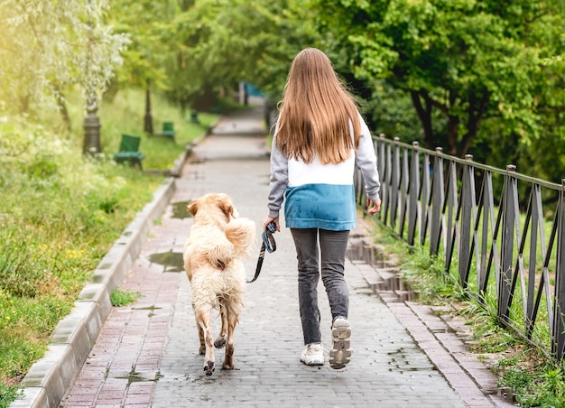 Rear view of young girl walking dog along wet park alley
