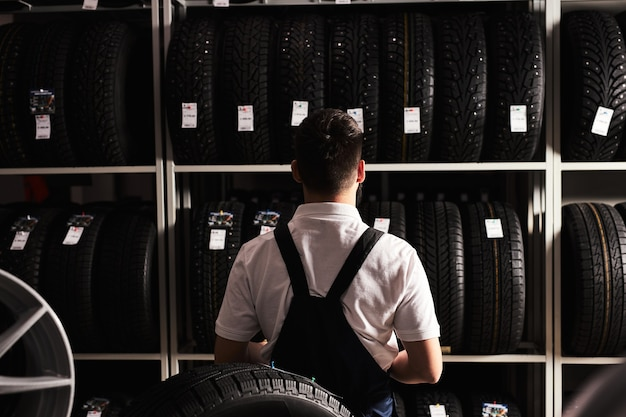 Rear view on young male mechanic with looking at car tires in automobile service center, wearing uniform. at work