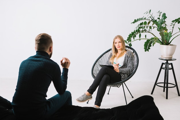 Rear view of a young man discussing her problems with female psychologist sitting on chair in office