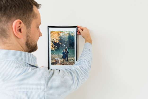 Rear view of a young man holding his family picture frame on white wall
