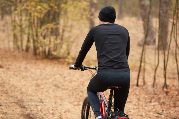 Rear view of a young man riding bicycle on beautiful nature background. back view of sportsman wearing black track suit and cap, enjoying cycling in forest. healthy lifestyle and sport concept.