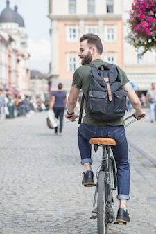 Rear view of a young man riding bicycle in city