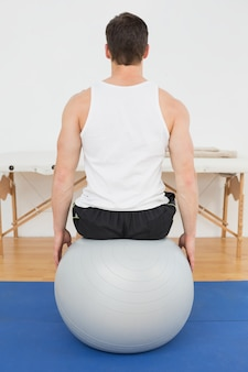 Rear view of a young man sitting on yoga ball