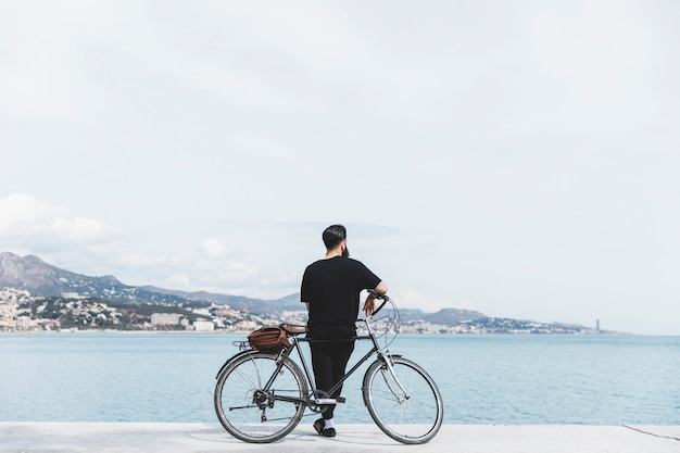 Rear view of a young man standing with bicycle looking at sea