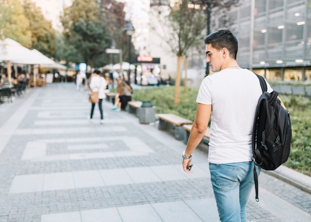Rear view of a young man walking on pavement