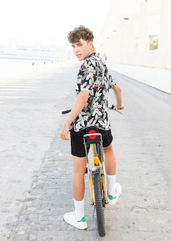 Rear view of a young man with bicycle looking at camera