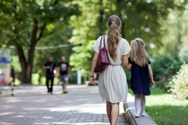 Rear view of young mother walking with little girl
