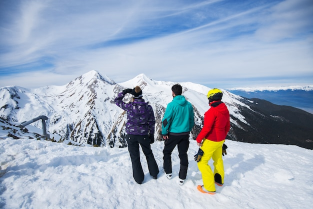 Rear view of young people enjoying in snowy winter on the top of the mountain