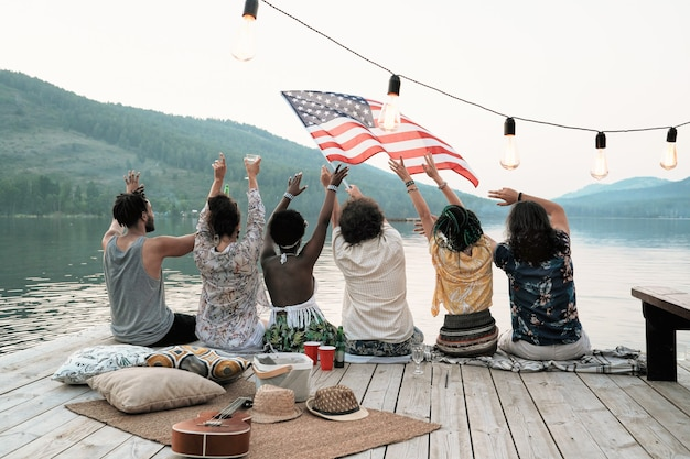 Rear view of young people sitting on a pier with american flag and celebrating the holiday on the nature