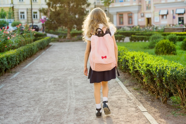 Rear view of young schoolgirl in uniform with backpack